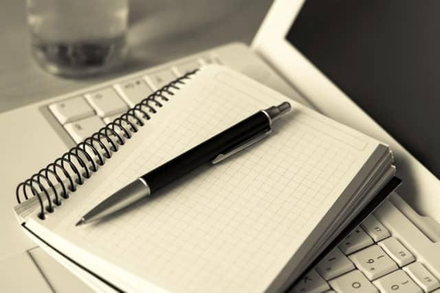 Mesa con ordenador, cuaderno y boli