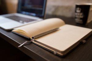 Libro con ordenador y material para escribir