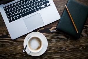 Ordenador, café, cuaderno y boligrafo.